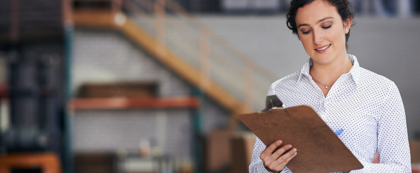 Woman in dress shirt holding a clipboard