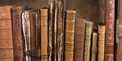 Old books with brown bindings and open bindings standing up