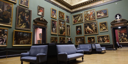 Room with paintings on wall and blue couches