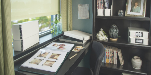 Desk with white boxes, scrapbook and bookcase