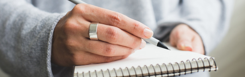 Person wearing grey sweater holding a pencil over a spiral bound notebook