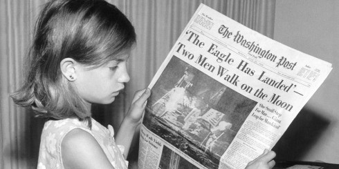 Young child holding newspaper about moon walk