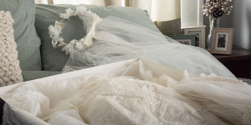 Wedding dress in box with veil on bed