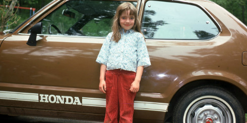 girl standing in front of brown car