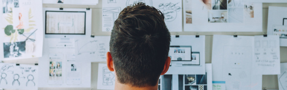 Person with short hear in front of a wall covered in papers