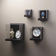 Square wall-mounted exhibit cases displaying vases and plates on neutral background
